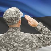 Soldier in hat facing national flag series - Estonia - stock photo