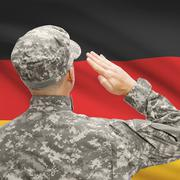 Soldier in hat facing national flag series - Germany - stock photo