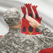 Soldier in hat facing national flag series - Gibraltar - stock photo