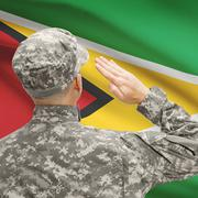 Soldier in hat facing national flag series - Guyana - stock photo