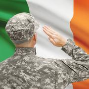 Soldier in hat facing national flag series - Ireland Stock Photos