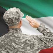 Soldier in hat facing national flag series - Kuwait - stock photo
