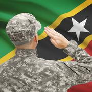 Soldier in hat facing national flag series - Saint Kitts and Nevis Stock Photos