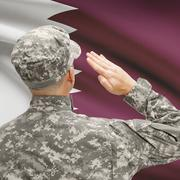 Soldier in hat facing national flag series - Qatar - stock photo