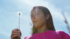 Attractive young woman outdoors, blowing on a dandelion on a summer day - stock footage