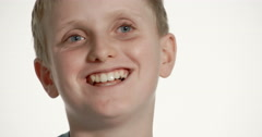Blond preteen boy laughing and chatting happily in close up Stock Footage