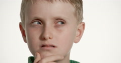 Suspicious blond preteen boy looks from side to side warily, hand on chin Stock Footage