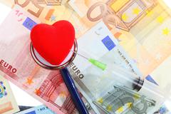 cost of health care: stethoscope red heart on euro money - stock photo