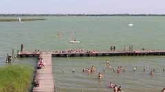 People swimming in lake, jetty and yachts Stock Footage