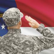 Soldier saluting to US state flag series - North Carolina - stock photo