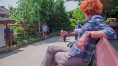 Viewers sitting on bench during bouling game Stock Footage