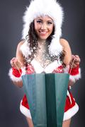 sexy girl wearing santa claus clothes with magic color bag - stock photo