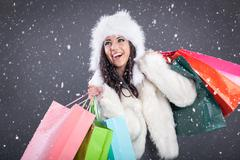 portrait of a beautiful young woman in a white fur coat holding  color bag - stock photo