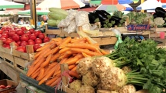 Celery and carrots on stall, tomatoes behind, people passing in background. 4k Stock Footage
