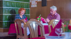 Senior couple unfolding their napkins in a restaurant Stock Footage