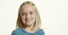 Pretty nine-year-old blonde girl smiles, looks down then up towards camera Stock Footage