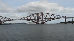 Train crossing Forth Rail Bridge with cruise ship Scotland - stock footage