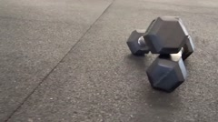 Two dumbbells on athletic flooring - stock footage
