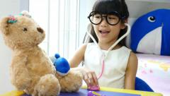 Asian girl playing doctor with doll Stock Footage