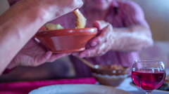 An old woman is putting some masked potatoes on her plate Stock Footage