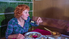 A senior woman enjoying her meal in a restaurant Stock Footage
