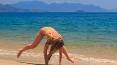 Blonde girl in bikini makes split on wet sea sand wave hands Stock Footage