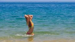 Blond slim girl in bikini swings splashes in azure sea Stock Footage