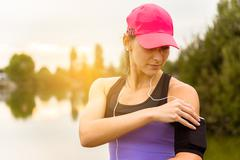 Runner woman hearing music after the run. Stock Photos