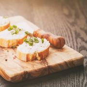 Crunchy baguette slices with cream cheese and green onion on olive board Stock Photos