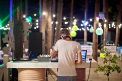 DJ at work in outdoor cafe, night photo - stock photo