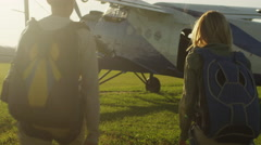 Man and Girl with Parachutes Moving towards the Plane Stock Footage