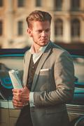 Confident wealthy young man with newspaper near classic convertible - stock photo