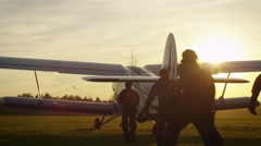 Group of Skydivers Moving Towards Airplane in Sunset Light - stock footage
