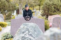 Senior lady in black at the grave of a loved one - stock photo
