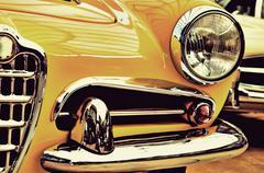 The hood, bumper, headlight and radiator of stylish yellow vintage car. Vinta - stock photo