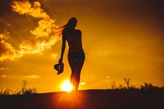 woman girl goes on road travel tourism silhouette holding a hat - stock photo