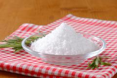 Coarse grained edible salt on small glass plate - stock photo