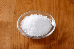 Stock Photo of Coarse grained edible salt on small glass plate