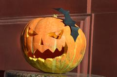 Pumpkin carved with a smile and bats (Halloween background for a party flyer) - stock photo