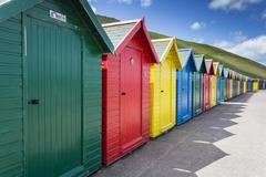 Row of colourful beach huts and their shadows with green hill backdrop, West Stock Photos
