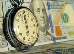The Chronometer on the background of dollar bills (time - money, income, loan - stock photo