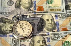 Stopwatch on the background of dollar bills (time - money, income, loan - con Kuvituskuvat