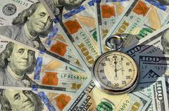 Stopwatch on the background of dollar bills (time - money, income, loan - con - stock photo