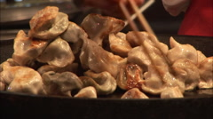 Chef cooking Chinese potsticker dumplings - stock footage