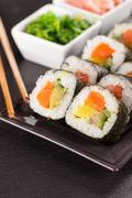 sushi pieces with chopsticks - stock photo