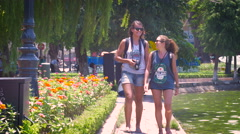 Two young college aged woman travel together as tourists in park taking photos. Stock Footage