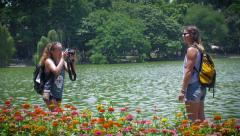 Two young women travelers take tourist photos of one another on lake - stock footage