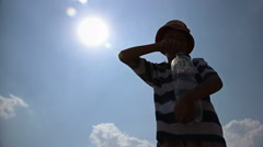 Intense heat, the boy drinks water and pours it in the sun, thirst, sunstroke Stock Footage