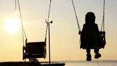 Boy on a swing at sunset a boy on a swing at dawn, silhouette, river Stock Footage