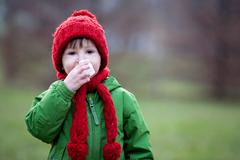 Little boy, sneezing and blowing his nose on a sunny winter day Stock Photos